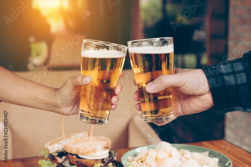 Close up teenager friends toasting and clinking with glass of beer.