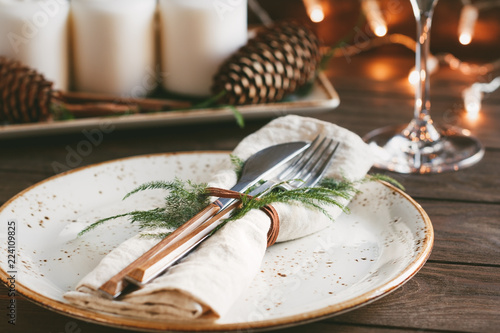 Obraz Thanksgiving table setting among white candles and cones. Ceramic plate with fork and knife on a linen napkin. The concept of a festive dinner. - fototapety do salonu