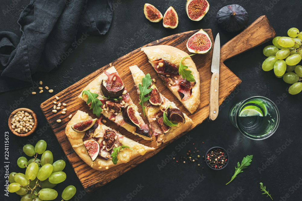 Fototapety, obrazy: Flatbread with figs, prosciutto, grapes, arugula on wooden serving board. Top view, toned image. Sliced pizza