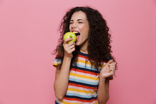Photo Of Beautiful Woman 20s With Curly Hair Eating Green Apple, Isolated Over Pink Background