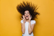 Leinwanddruck Bild - Photo of caucasian woman 20s laughing and having fun with shaking hair, isolated over yellow background