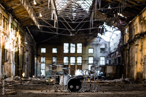 A white drum set stands in an abandoned hangar, an abandoned red brick plant. devastation, post apocalypse, urbex