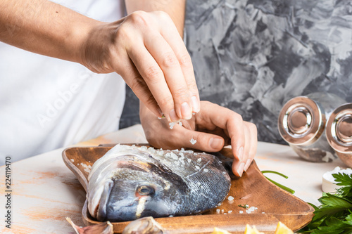Fotomural  Process of cooking Dorado fish with lemon, olive oil and herbs