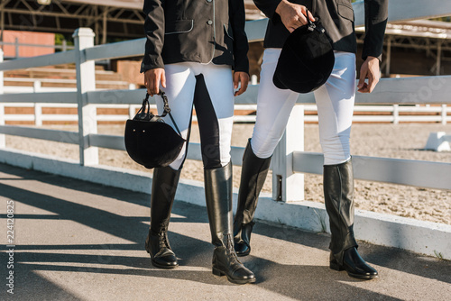 Fototapeta cropped image of equestrians in professional apparel walking near fence and holding riding helmets at ranch obraz