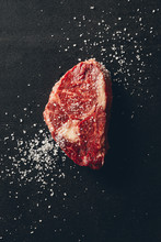 Top View Of Raw Meat Steak And Salt On Surface In Kitchen