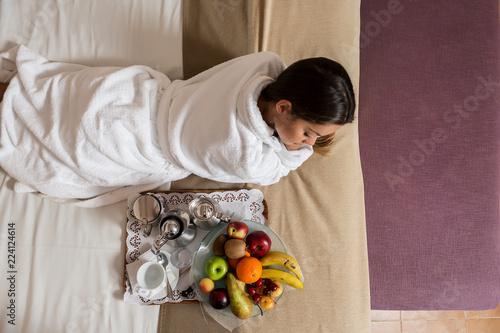 Foto op Aluminium Assortiment Woman lying on bed near plate of fruits