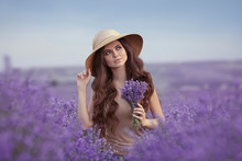 Adorable Young Woman Portrait In Straw Hat Over Purple Lavender Field. Attractive Girl With Long Curly Hair Holding Violet Flowers In Hand. Carefree Brunette Enjoying Life And Dreaming At Sunset.
