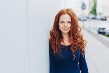 Freundliche Rothaarige Frau Lehnt Draußen An Einer Weißen Hauswand
