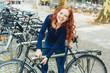 canvas print picture - fröhliche studentin schließt ihr fahrrad ab