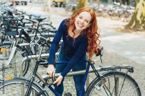 fototapeta na ścianę fröhliche studentin schließt ihr fahrrad ab