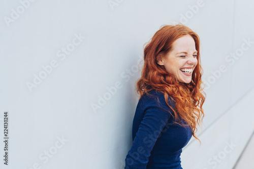 Fotografia lachende frau steht vor einer weißen wand