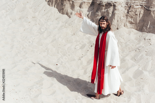 Photo high angle view of Jesus in robe, red sash and crown of thorns showing way in de