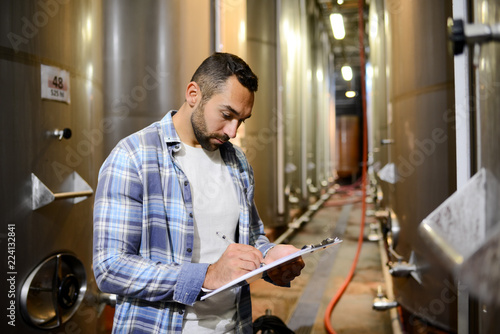 Fotomural  handsome man winemaker in a winery wine cellar during harvest season with stainl