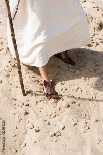 Photo cropped image of Jesus in robe and sandals walking in desert with wooden staff