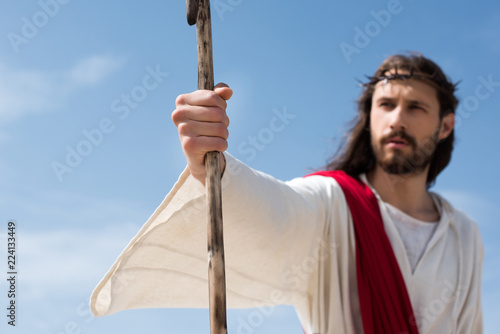 selective focus of Jesus in robe, red sash and crown of thorns holding wooden st Wallpaper Mural