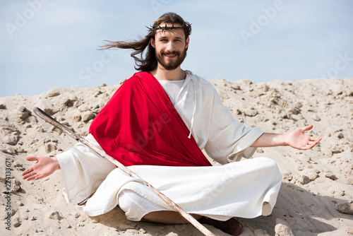 smiling Jesus in robe, red sash and crown of thorns sitting in lotus position wi Fototapete