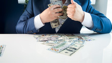 Closeup Photo Of Greedy Covetous Businesman Filling His Pockets With Stacks Of Money