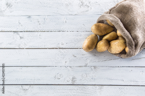Ripe potatoes in burlap sack freely lying on wooden board