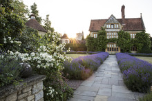 View Of Historic Manor House From Across A Walled Garden With Lawn, Path And Flowerbeds.