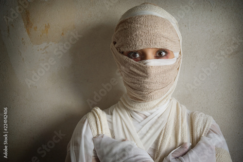 Fotografering woman wrapped in bandages as egyptian mummy halloween costume