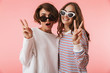 canvas print picture - Women friends isolated over pink wall background showing peace gesture.