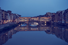 """Famous Bridge """"Ponte Vecchio"""" In Florence In Italy At Night / Illuminated Bridge With Nice Reflections In The Water"""
