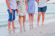 Family of four is standing barefoot on the seashore