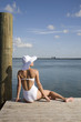 Young woman in white swimsuit and sun hat sitting on pier
