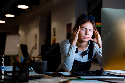 Young woman graphic designer using pc computer working at night in office.