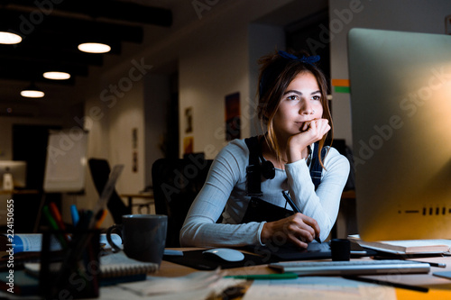 Young woman graphic designer using pc computer working with tablet at night in office Fototapet