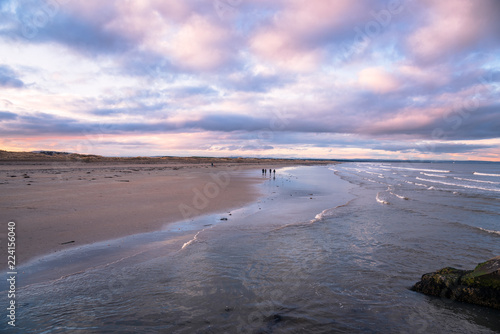 People Waking and Enjoying the Scenery on a Beautiful Sandy Beach at Sunset in Winter. St. Andrews, Scotland.