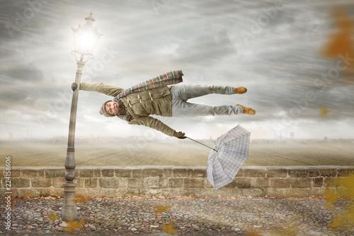 Fototapeta Mann in einem kräftigen Herbstturm