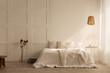 Leinwanddruck Bild - Lamp above white bed with pillows in minimal bedroom interior with plants and stool. Real photo