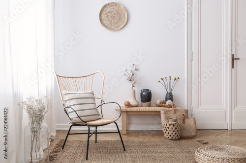 Fotografie, Obraz  Flowers on wooden stool next to armchair in white loft interior with pouf and plate