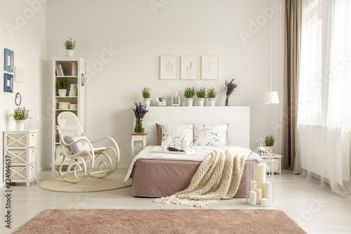 Rocking chair next to bed with blanket in spacious white ...