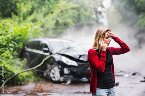 Obraz na plátně A young woman with smartphone by the damaged car after a car accident, making a phone call