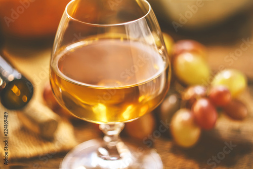 glass with wine on a background of grapes on a wooden table