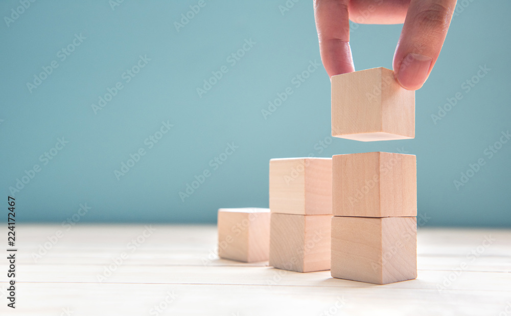 Fototapeta Hand arranging wood cube stacking as step stair. Business concept growth success process on blue background, copy space.