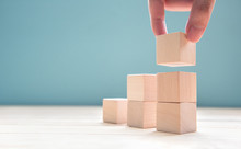 Hand Arranging Wood Cube Stacking As Step Stair. Business Concept Growth Success Process On Blue Background, Copy Space.