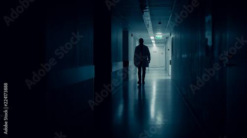 Tableau sur Toile Medical Doctor Silhouette Walks in Dark Part of the Hospital Corridor
