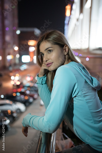 Woman silently standing on the terrace and looking around, night city background