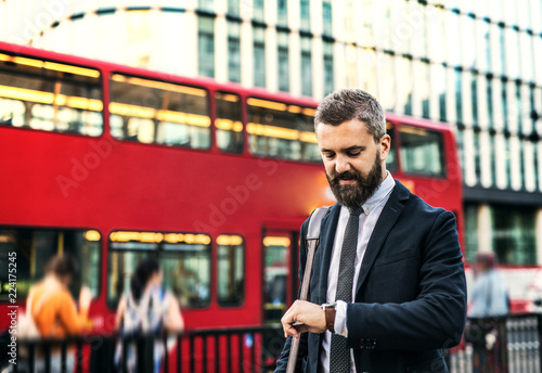 Foto op Canvas Londen rode bus Hipster businessman waiting for the bus in London, checking the time.