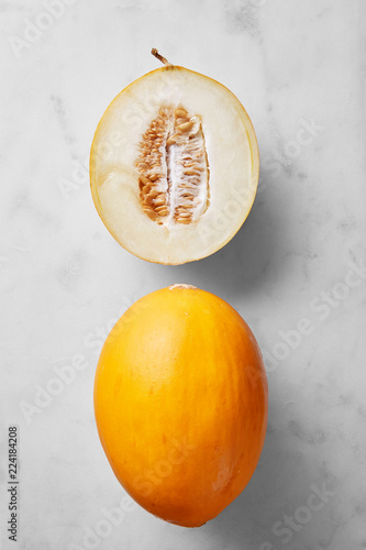 Mellon fruit half and whole isolated on a marble background viewed from above. Top view
