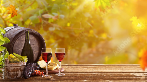 Vines with grapes and old cask on vintage wooden table.