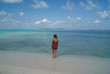 Young girl watching the skyline in a paradise beach of Maldives islands