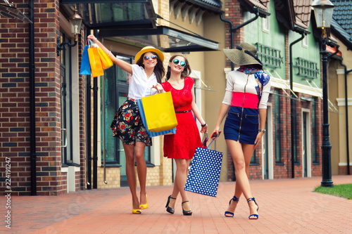 plakat Pretty happy bright women female girls friends in colorful dresses, hats and high heels with shopping bags walking at street after shopping in shopping mall in summer. Shop sales, black Friday.