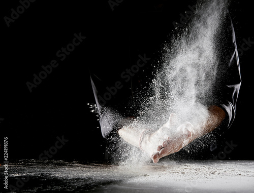 Poster Pizzeria Cloud of flour spraying into air as man rubs hands