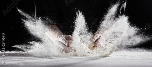 Leinwand Poster Flour flying into air as chef slams dough on table