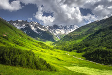 Alpine Mountains Landscape On Bright Sunny Summer Day. Grassy Meadow On Hillside With Mountain River And Rocky Mountain Covered By Snow. Blue Sky With Clouds Over Mountain Range. Vibrant Highlands