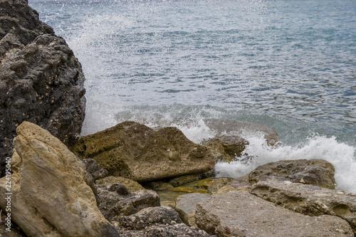 Coast stones with white spray on Corfu / Greece